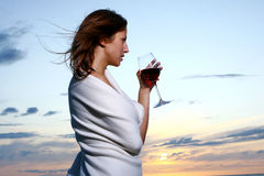 Beautiful young woman drinking wine on beach Royalty Free Stock Images
