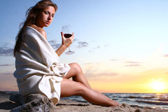 Beautiful young woman drinking wine on beach Stock Photo