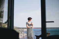 Beautiful young woman drinking wine and standing on a balcony with beautiful ocean view Stock Photo