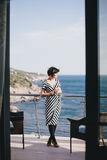 Beautiful young woman drinking wine and standing on a balcony with beautiful ocean view stock photos
