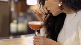 Beautiful young woman drinks clover club cocktail in the pub. Beautiful young woman drinks clover club cocktail. Pretty brunette enjoys evening relax in the pub stock footage