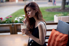 Beautiful young woman drinks coffee in a cafe on the terrace in summer Stock Images