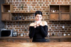 Beautiful young woman drinks coffee from a white cup in the kitc. Beautiful girl with a short haircut drinks tea with a white cup in the kitchen, fun, fragrance Stock Photography