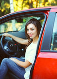 Beautiful young woman driver behind wheel red car Stock Images
