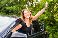 Beautiful young woman driver showing car keys in hand.  Stock Image