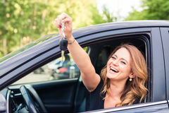Beautiful young woman driver showing car keys in hand.  Royalty Free Stock Photo