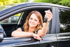 Beautiful young woman driver showing car keys in hand.  Royalty Free Stock Image