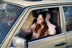 Beautiful young woman driving her car in the summer in the city royalty free stock photography