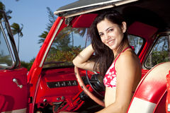 Beautiful young woman driving old convertible car. Pretty teenager with bikini in red vintage car Stock Images