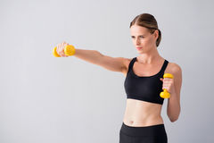 Beautiful young woman with dumb bells. Sport fun. Content and cheerful young woman using dumb bells while standing on isolated grey background Royalty Free Stock Photos