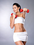 Beautiful young woman with dumbbells. Grey studio background. Healthy lifestyle concept Royalty Free Stock Image