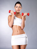 Beautiful young woman with dumbbells. Grey studio background. Healthy lifestyle concept Royalty Free Stock Photos