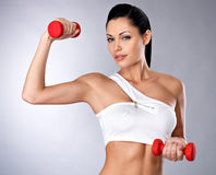 Beautiful young woman with dumbbells. Portrait of beautiful young woman with dumbbells -  grey studio background. Healthy lifestyle concept Royalty Free Stock Photos