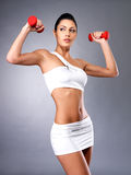 Beautiful young woman with dumbbells. Grey studio background. Healthy lifestyle concept Royalty Free Stock Images
