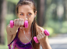 Beautiful young woman with dumbbells. Exercising in the park. Outdoor background. Healthy lifestyle concept Royalty Free Stock Photo