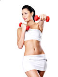 Beautiful young woman with dumbbells. Grey studio background. Healthy lifestyle concept Royalty Free Stock Photo