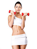 Beautiful young woman with dumbbells. Grey studio background. Healthy lifestyle concept Stock Images
