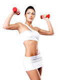 Beautiful young woman with dumbbells. Grey studio background. Healthy lifestyle concept Stock Photos