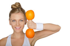 Beautiful young woman with dumbbells oranges. Beautiful young woman with dumbbells two ripe oranges isolated on white Stock Photo