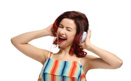 Beautiful young woman with dyed curly hair listening music. On white background Stock Photo