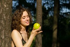 Beautiful young woman eating apple outdoors Royalty Free Stock Images