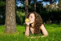 Beautiful young woman eating apple outdoors Stock Photos