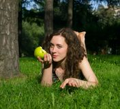 Beautiful young woman eating apple outdoors Royalty Free Stock Image