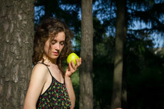Beautiful young woman eating apple outdoors Stock Images