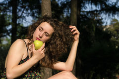 Beautiful young woman eating apple outdoors Stock Photo
