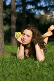 Beautiful young woman eating apple outdoors Royalty Free Stock Photos