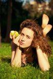 Beautiful young woman eating apple outdoors stock image