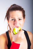 Beautiful young woman eating an apple. Portrait of beautiful young woman eating an apple stock photo