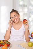 Beautiful young woman eating an apple while talking on the phone Stock Photo