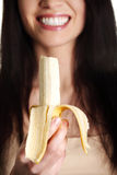 Beautiful young woman is eating banana. Royalty Free Stock Photography