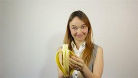 Beautiful young woman eating banana stock footage