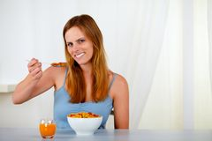 Beautiful young woman eating breakfast Stock Images