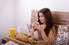 Beautiful young woman eating breakfast in bed in the morning Stock Photography