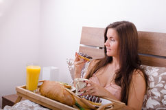 Beautiful young woman eating breakfast in bed in the morning Stock Images