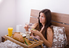 Beautiful young woman eating breakfast in bed in the morning Royalty Free Stock Photos