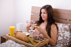 Beautiful young woman eating breakfast in bed in the morning Royalty Free Stock Image