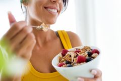 Beautiful young woman eating cereals and fruits at home. Royalty Free Stock Photography