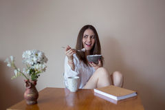 Beautiful young woman eating cereals. Young girl eating healthy food Stock Photo
