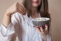 Beautiful young woman eating cereals Royalty Free Stock Photo