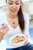 Beautiful young woman eating cereals at home. Stock Photography