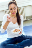 Beautiful young woman eating cereals at home. Stock Images