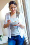 Beautiful young woman eating cereals at home. Royalty Free Stock Images
