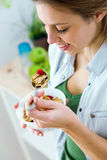 Beautiful young woman eating cereals in the kitchen. Royalty Free Stock Photography