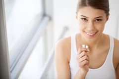 Beautiful young woman eating chewing gum, smiling.  royalty free stock photos