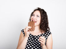 Beautiful young woman eating a chocolate bar, wears a dress with polka dots.  Stock Photos