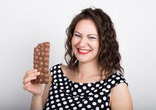 Beautiful young woman eating a chocolate bar, wears a dress with polka dots.  Stock Images